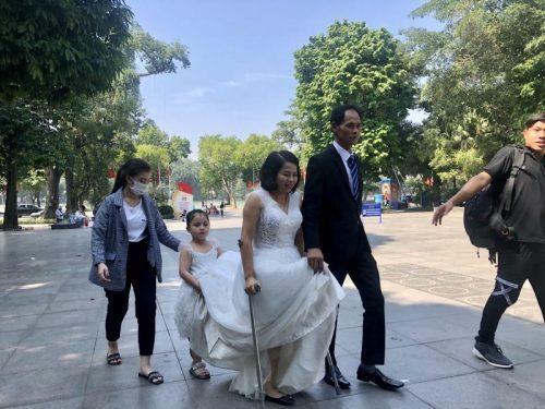 Cô bé Nguyễn An Nhiên đỡ váy cưới cho mẹ. Chị Nguyễn Thị Hương, mẹ của em vừa mới cắt đi một chân vào 3 năm trước. (Ảnh: Quỳnh Anh)